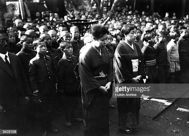 Wives of the Japanese Mixed Brigade Commander of Manchuria Suzuki and school children living in the neighbourhood pray at the Hikawa Shrine for the...