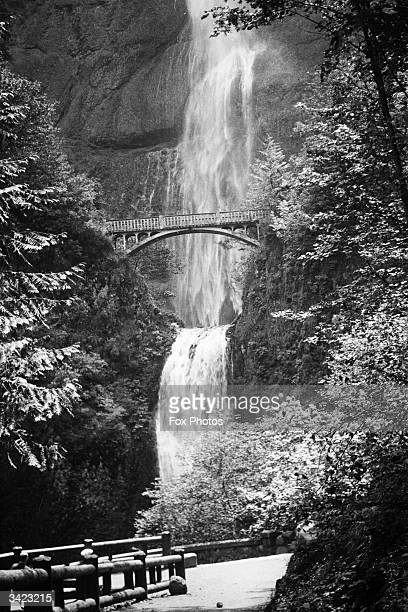Foot high Multnomah Falls, Columbia River Highway, Oregon, the fourth highest in the USA, dwarf a bridge in front of them.