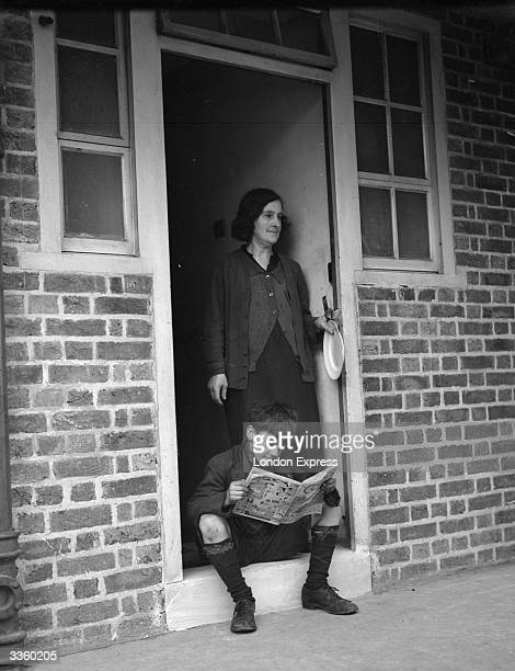A boy reads a comic sitting on the doorstep of his home at Hillcott House a new block of council flats in Shoreditch London his mother stands behind...