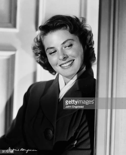 Happy film star; Ingrid Bergman leans against a doorway.