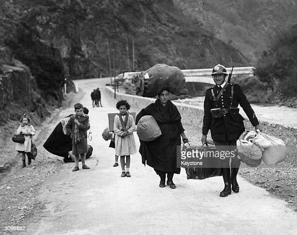 A member of the French frontier troops helps a family of refugees cross the border from Spain during the Spanish Civil War