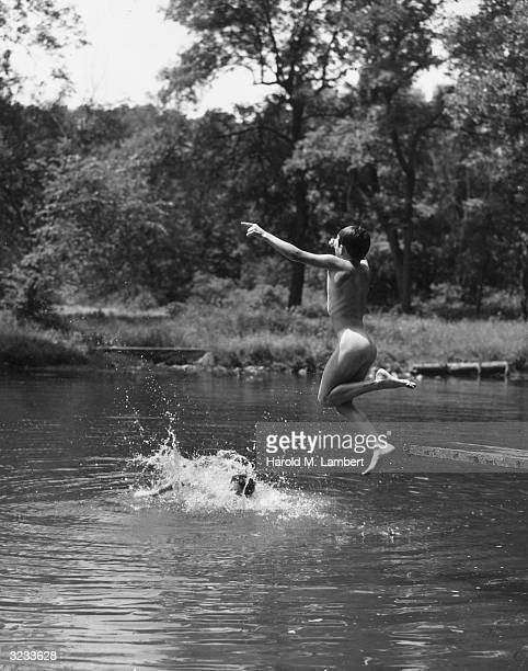 A naked boy jumps from a board into a lake while another boy splashes in the water