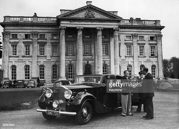 A wealthy man shaking hands with a representative of the Moor Park Golf Club Rickmansworth Hertfordshire as he and his chauffeur prepare to leave the...