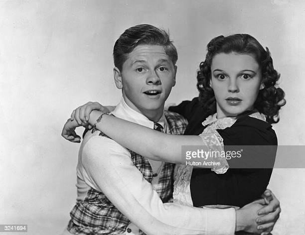 American actors Mickey Rooney and Judy Garland hug and look at the camera with surprised expressions in a promotional portrait for director George B...
