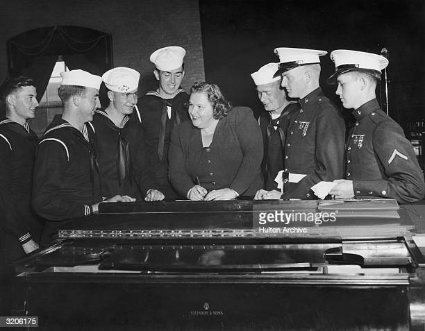 American vocalist Kate Smith smiles as she signs autographs for a group of uniformed sailors