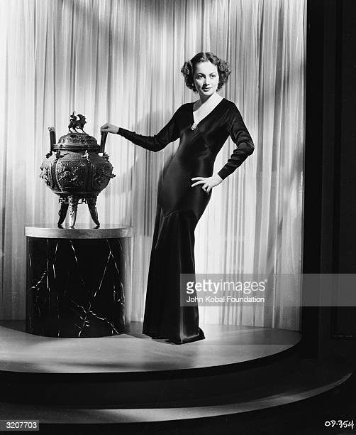 Britishborn actress Olivia de Havilland fingers a threelegged Oriental cauldron She is wearing a floorlength black satin gown with a plunging neckline