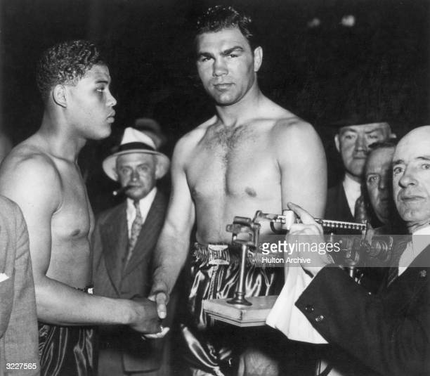 German boxer Max Schmeling shakes hands with American boxer Joe Louis while being weighed in before one of their fights