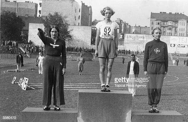 Grethe Whitehead British winner of the 80 metres hurdles with secondplaced Dempe of Germany giving the Nazi salute at the High School World...