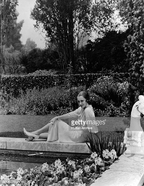 Hollywood screen star Olivia De Havilland relaxes in the garden of her new home in Hollywood