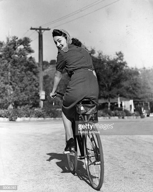 Hollywood screen star Olivia De Havilland riding a bicycle
