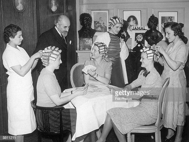 Monsieur Gaston Bondon seen here chatting with beauty queens who were playing bridge while trying out a new method of permanent waving