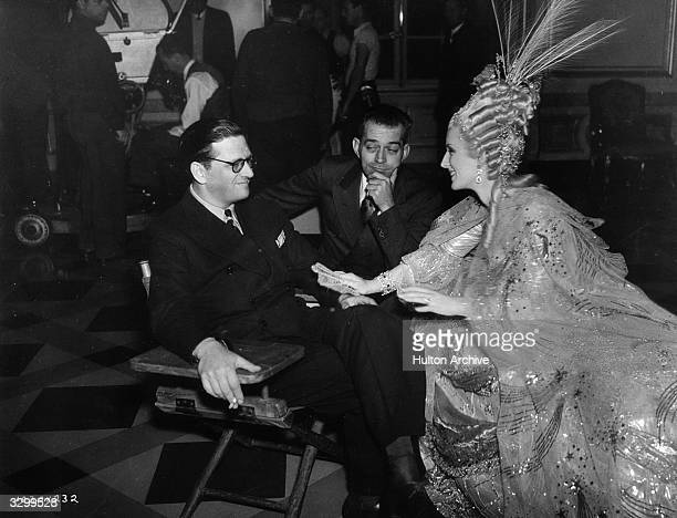 Norma Shearer talks with Hunt Stromberg the producer and director W S Van Dyke on the set of 'Marie Antoinette' an MGM film about the ast days of the...
