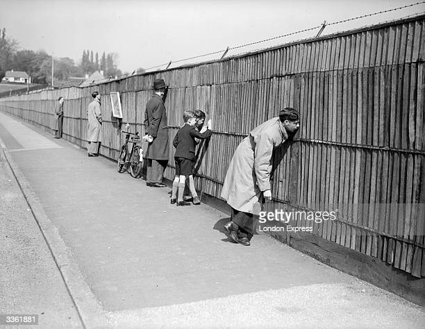 People watching through holes in the fence the secret tennis trial held at the All England Tennis Club Wimbledon London