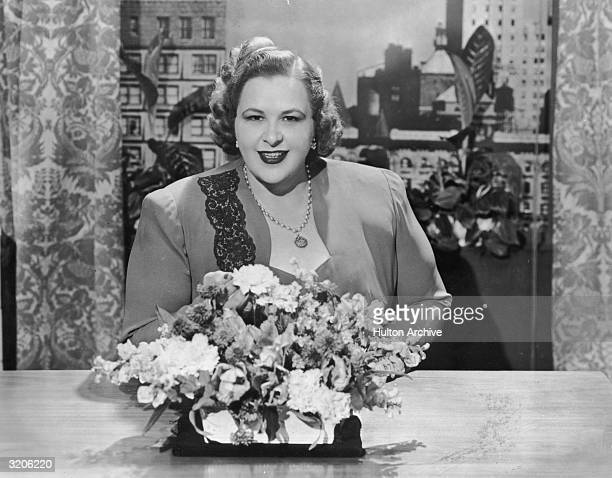 Portrait of American vocalist Kate Smith seated at a table behind a bouquet of flowers Smith wears a dress suit and a pendant around her neck