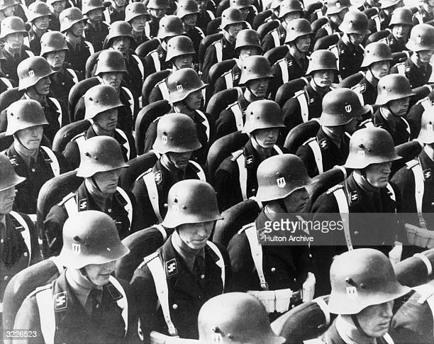 Rows of Nazi SS troops also known as the Schutzstaffel stand in uniform at Nuremberg Germany They wear helmets with a double lightning bolt emblem