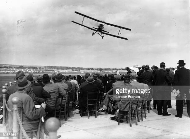 Spectators watch a low flying Tiger Moth biplane compete in an air race