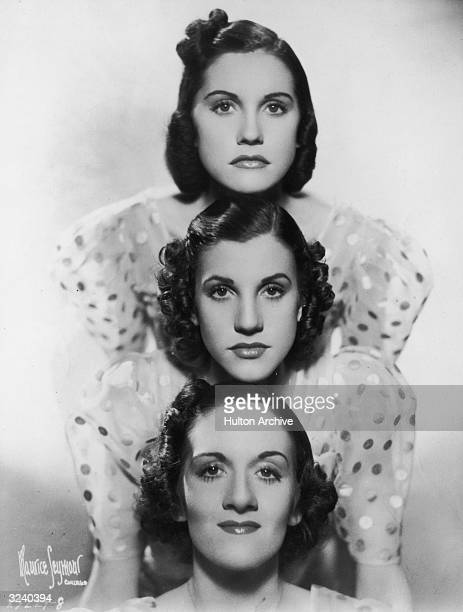 Studio portrait of the singing group the Andrew Sisters wearing matching polka dot dresses Top to bottom Maxene Andrews Patty Andrews and LaVerne...