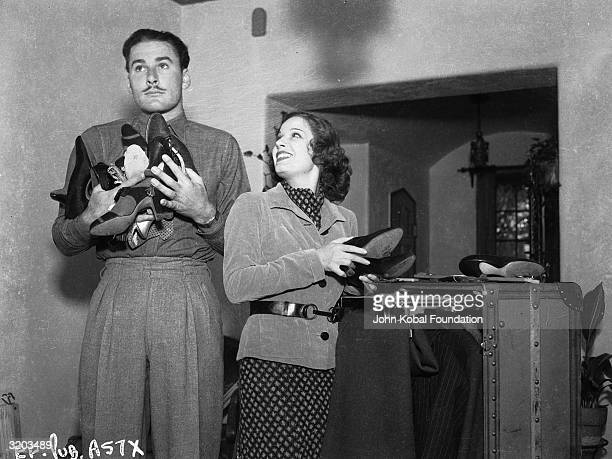 Tasmanian film star Errol Flynn and his first wife French actress Lili Damita sort out a pile of shoes
