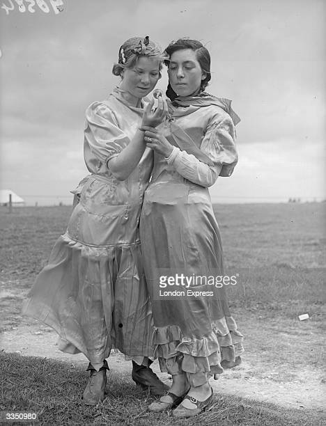 Two Romany cousins looking into a crystal ball on the Epsom Downs before the Derby. They claim to see racehorse Golden Sovereign in their crystal.