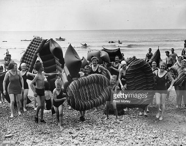 Workers and their families carrying lilos on to the beach as they enjoy a company day out at Brighton