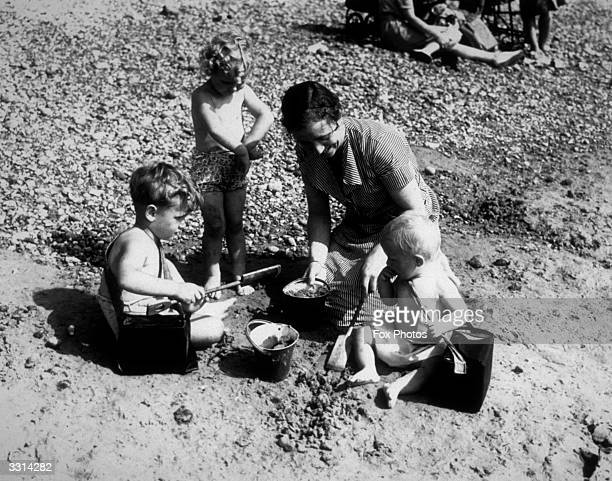 Family on the beach at Brighton, with gas masks at the ready.