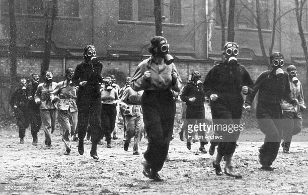 A group of German women take part in an exercise run while wearing their gas masks