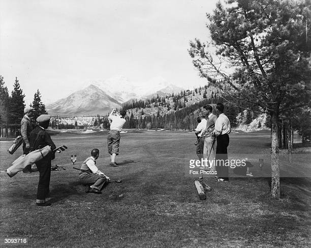 A group of men playing golf on Banff Springs golf course