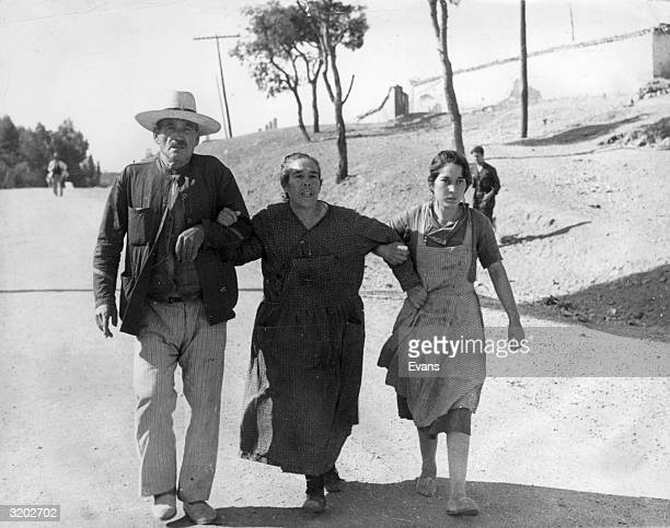 A group of refugees cling to one another as they prepare to cross the border into France to escape the Spanish Civil War
