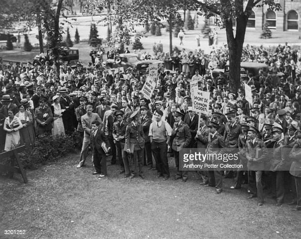 A large group of American male ROTC students gather to protest the US draft late 1930s They hold signs reading 'We Won't be Cannon Fodder' and...