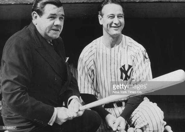 American baseball players Babe Ruth and Lou Gehrig pose together with baseball bats in the Yankees dugout New York City Ruth wears a suit while...