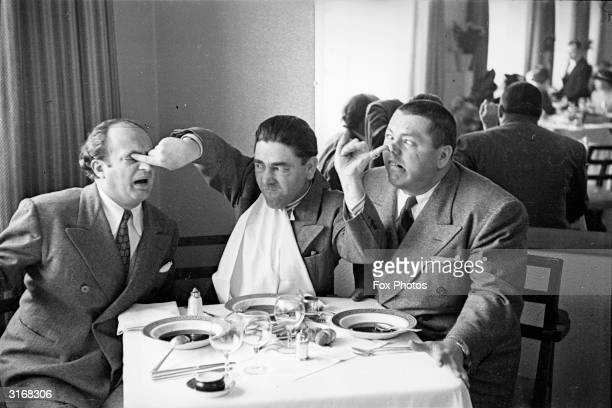 American comedian Moe Howard poking his fellow comedians Larry Fine in the eye while sticking a finger up the nose of Curly Howard The trio starred...
