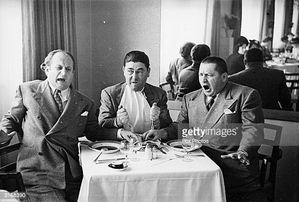 American comedian Moe Howard stabbing his fellow comedians Larry Fine and Curly Howard with forks The trio starred in countless films together as...