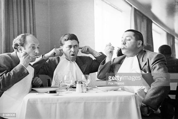 American comedian Moe Howard sticking his fingers in his ears while his fellow comedians Larry Fine and Curly Howard noisily eat soup The trio...
