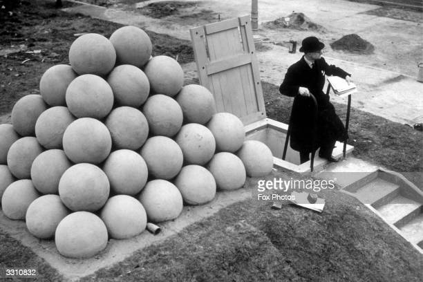 An ARP warden coming out of an air raid shelter on display at the British Industries Fair The shelter has a bomb deflector on the roof consisting of...