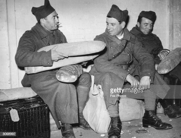 French soldiers carry large loaves of bread on their journey to the front from Paris