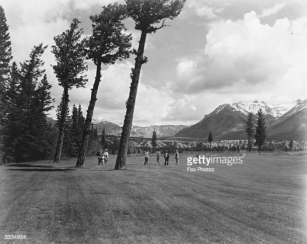 Golfers on the fairway of the 16th Green by the Three Sentinels on the Banff Springs golf course