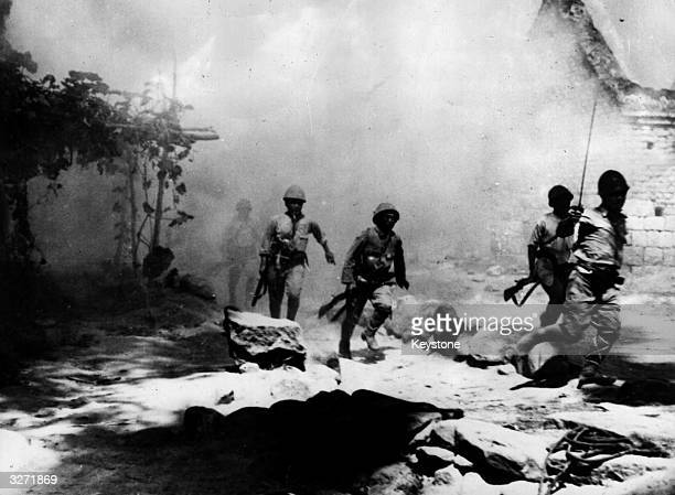 Japanese troops rushing in to attack the burning camp of Chinese soldiers at Vhangsha one of the most important of Chiang Kai Shek's positions