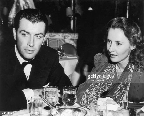 Married American actors Robert Taylor and Barbara Stanwyck sit at a table in a restaurant wearing formal attire Stanwyck wears a cast on her forearm...