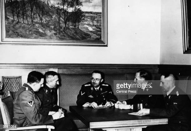 Nazi police leader Heinrich Himmler centre briefs SS commanders Reinhard Heydrich Heinrich Muller Artur Nebe and Huber on the day's work at Gestapo...