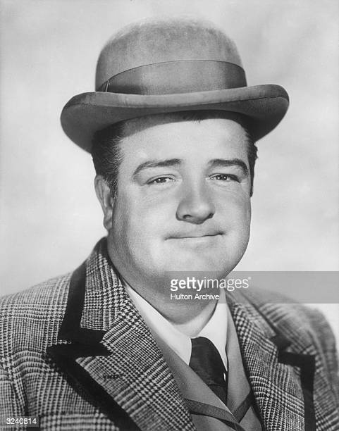 Studio headshot portrait of American actor and comedian Lou Costello grinning wearing a bowler hat and a tweed sport coat
