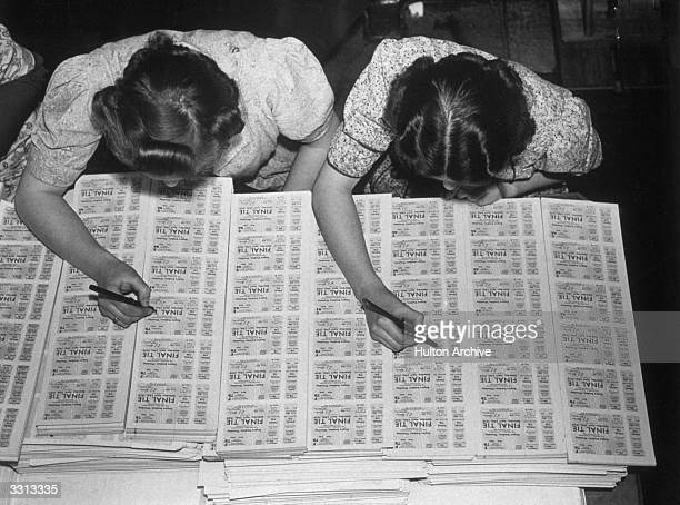 Two women checking FA cup final tickets at Messrs Waterlow's printing works in Finsbury London