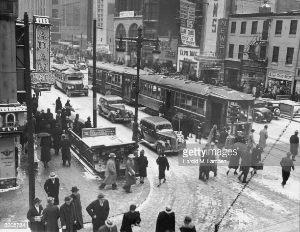View of a snow-covered downtown intersection with streetcars, automobile traffic and pedestrians, Philadelphia, Pennsylvania. Theater marquees and...