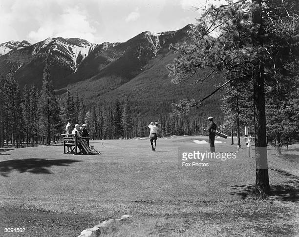Watched by companions a golfer tees off at the 17th hole at Banff Springs golf course