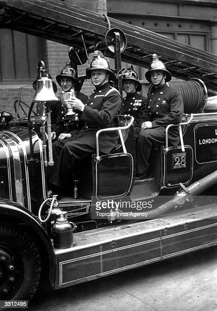 Whitechapel fireman holding the trophy they won in the 'Fire Brigades Escape Competition'