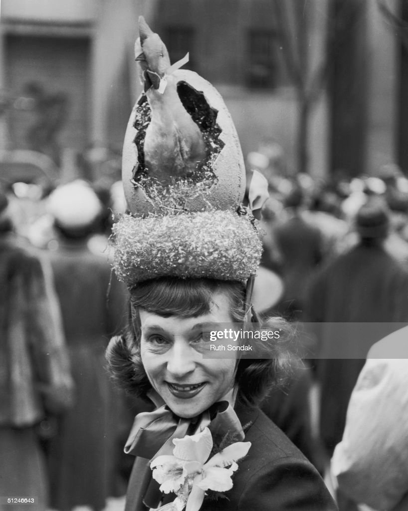 Circa 1940, A chicken hatches out of egg on a woman's hat, during an Easter parade in New York.