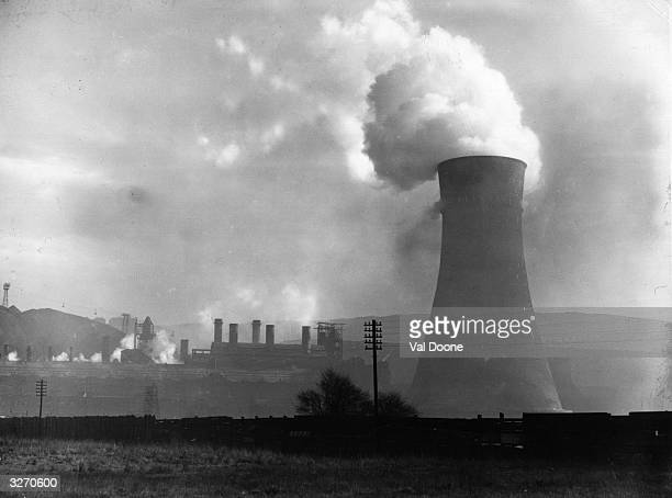 A cooling tower near the smoking chimneys of a factory on the outskirts of Sheffield in Yorkshire