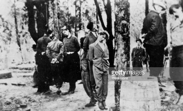A Gestapo agent inspects a group of Yugoslavs executed by Nazi henchmen