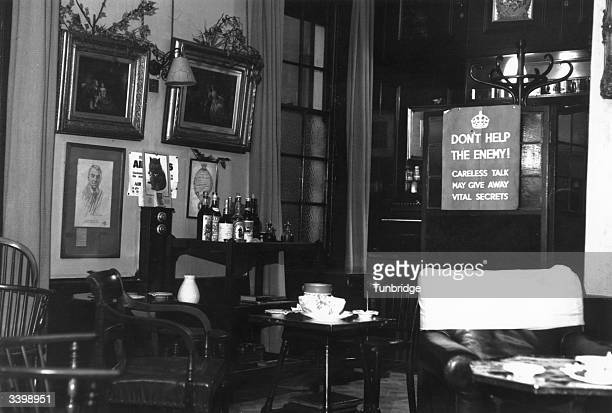 A government propaganda poster warning of the cost of careless talk displayed amongst the decoration at a wartime British pub