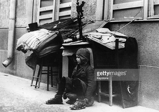 A little boy watches over his family's belongings which are piled up in the street while they arrange transport out of Helsinki The city has just...