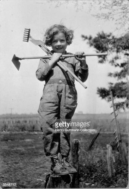 A little girl from Kansas posing with gardening tools
